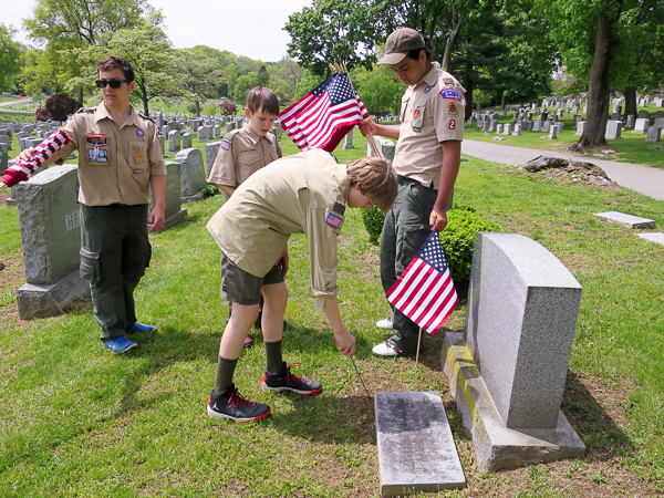 Placing flags for veterans at Mt. Hope Cemetery